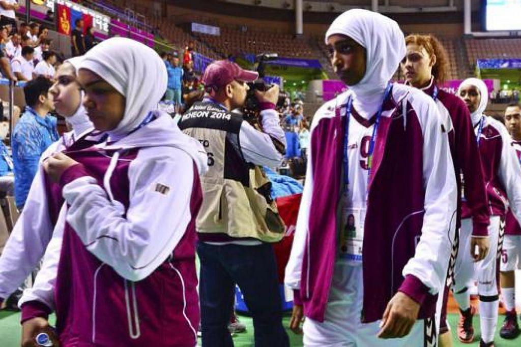 TARIK DIRI: Pasukan bola keranjang wanita Qatar meninggalkan gelanggang Selasa lalu. - Foto REUTERS