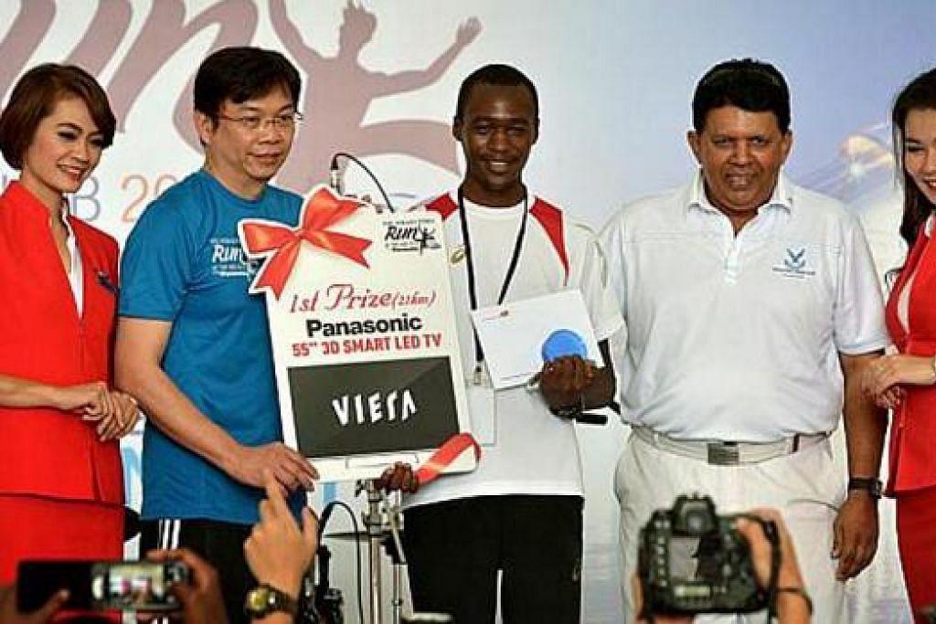 PEMENANG PERLUMBAAN UTAMA: Peserta Kenya, James Kemboi (tengah), 21 tahun, memenangi perlumbaan 21km. Bersama-sama beliau ialah Encik Daniel Tan, Pengarah Panasonic Singapore (kiri), dan Encik Patrick Daniel, Ketua Editor Divisyen Akhbar Bahasa Inggeris dan Melayu (EMND). - Foto-foto THE STRAITS TIMES