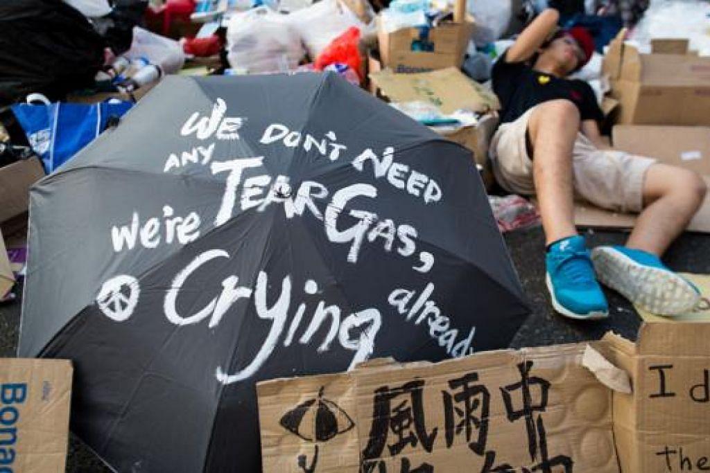 TERLENA SELEPAS BANTAHAN: Penunjuk perasaan terlena di Connaught Road semalam. Beribu-ribu penunjuk perasaan berkata mereka akan meneruskan bantahan di jalan-jalan raya di Hongkong. - Foto BLOOMBERG