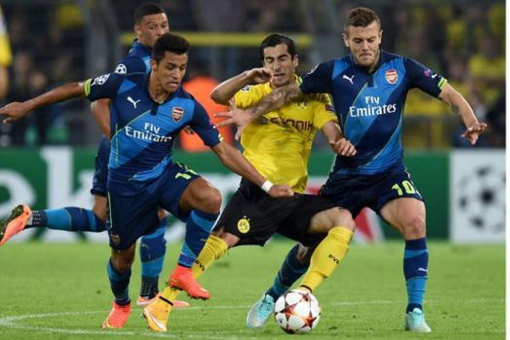 PERLU BANGKIT: Pemain Arsenal, Alexis Sanchez (kiri) dan Jack Wilshere (kanan), perlu bangkit dan membantu Arsenal memungut tiga mata maksimum di tempat sendiri selepas ia tewas kepada Borussia Dortmund dalam perlawanan pembukaan. - Foto AFP