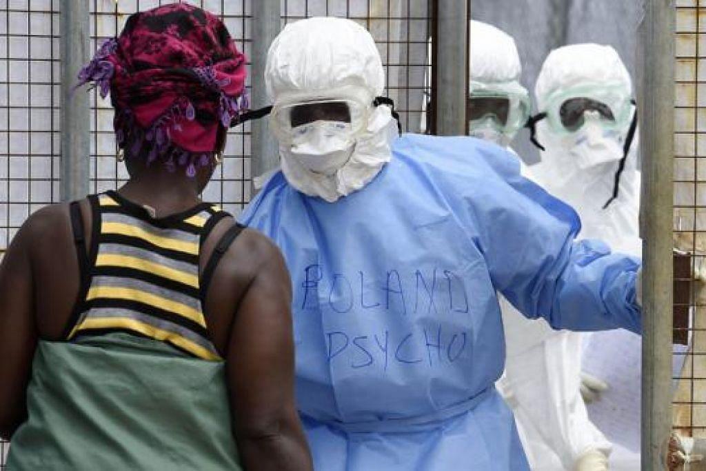 PENCEGAHAN EBOLA: Kakitangan hospital lengkap memakai pakaian pelindung menyambut seorang wanita yang menghantar makanan kepada sanak saudara di Hospital Island, Liberia. Pesakit Ebola pertama Amerika baru pulang dari negara itu. - Foto AFP
