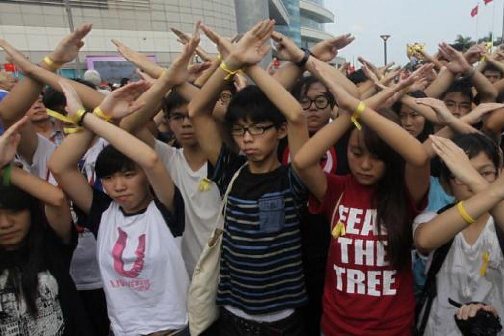 BELAKANGKAN SAMBUTAN: Penunjuk perasaan, Encik Joshua Wong (tengah), dan anggota prodemokrasi yang lain membuat gerak isyarat sewaktu upacara meraikan ulang tahun ke-65 China Komunis semalam. - Foto REUTERS