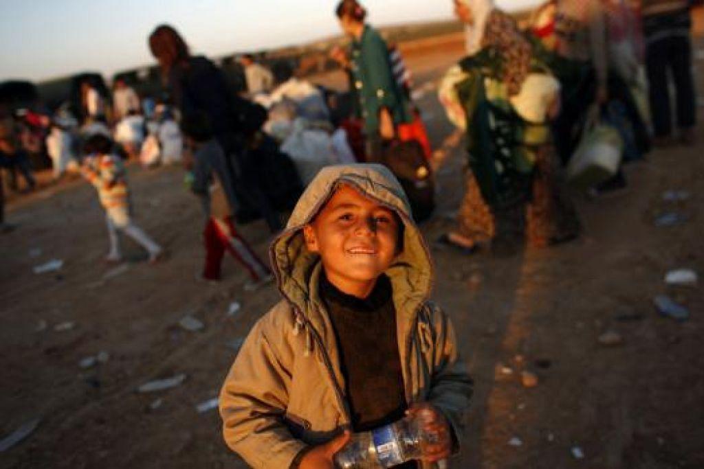 SELAMATKAN DIRI: Seorang kanak-kanak Kurdi Syria sempat menguntum senyuman semasa menunggu kenderaan untuk membawanya ke Turkey. - Foto REUTERS