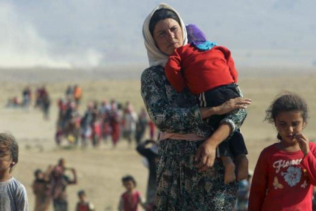 SELAMATKAN DIRI: Pelarian Syria bersama anak kecil dengan membawa barangan rumah melarikan diri ke sempadan Turkey-Syria daripada cengkaman pakatan Negara Islam (IS). - Foto-foto REUTERS