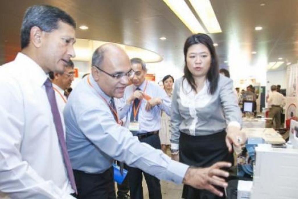 GALAK JIMAT TENAGA: Dr Vivian Balakrishnan (kiri) meninjau pameran yang diadakan sempena Anugerah Kerjasama Penjimatan Tenaga Nasional. - Foto ZAOBAO