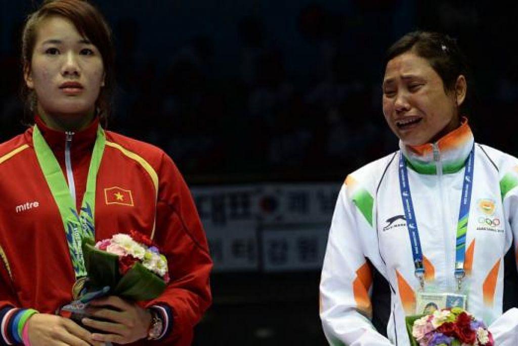 TAK MAHU PINGAT: Petinju India, Sarita Devi (kanan), menangis sambil enggan dikalung pingat gangsa yang dimenanginya. Di sebelahnya ialah peserta Vietnam, Luu Thi Duyen, yang berkongsi menang gangsa dalam acara tinju kelas 'light' dalam Sukan Asia Incheon ini. - Foto AFP