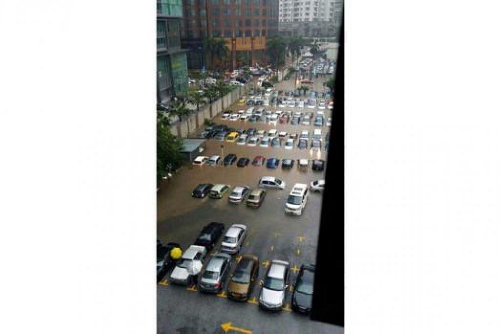 """DITENGGELAMI AIR: Ratusan kenderaan """"tenggelam"""" selepas sebuah tempat letak kereta di Jalan Kia Peng, Kuala Lumpur, dinaiki air sedalam kira-kira 0.6 meter berpunca daripada hujan lebat selama hampir dua jam. - Foto TWITTER"""