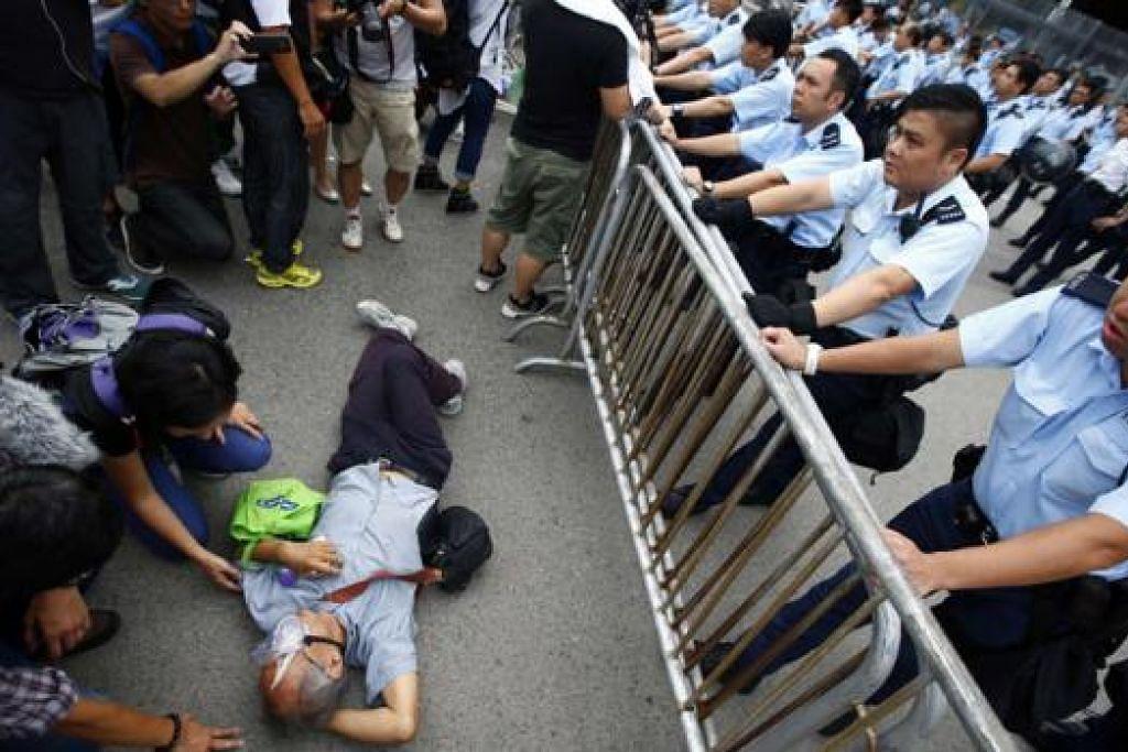 TERUS BANTAH: Polis memerhatikan gelagat seorang penunjuk perasaan yang baring di tempat masuk pejabat Ketua Eksekutif Hongkong, Encik Leung Chun-Ying. Encik Leung mahu membiarkan saja bantahan prodemokrasi berlanjutan sehingga mereka keletihan, namun para penunjuk perasaan bertegas akan tetap membantah selama yang boleh. - Foto REUTERS