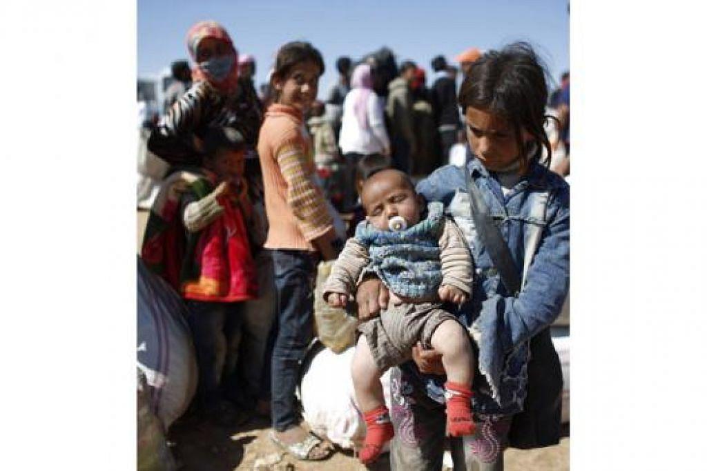 MENANTI DISELAMATKAN: Seorang kanak-kanak pelarian Kurdi Syria yang mendukung adiknya berusia tiga bulan sedang menunggu pengangkutan yang akan membawa mereka menyeberang masuk ke Turkey di Suruc, wilayah Sanliurfa. - Foto REUTERS