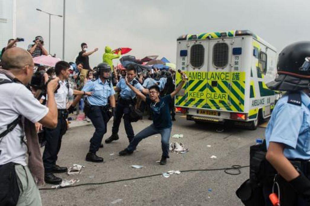 TERUSKAN BANTAHAN: Seorang penunjuk perasaan mahu merebahkan badannya di jalan raya demi memastikan tiada lagi kenderaan yang melepasi jalan raya itu selepas sebuah ambulans dibenarkan melepasi halangan di luar pejabat pemerintah Hongkong semalam. Ketegangan masih berlaku antara penunjuk perasaan prodemokrasi dan pasukan polis yang berkawal. - Foto AFP