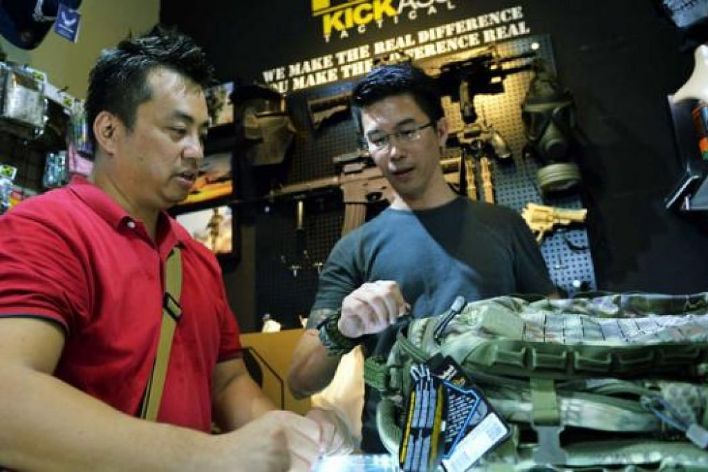 LAYAN PELANGGAN: Pemilik KICKAss Tactical di Beach Road Army Market, Encik Chris Woon (kanan), dengan pelanggannya, Encik Leroy Lam, yang ingin membeli beg stail tentera. - Foto KHALID BABA