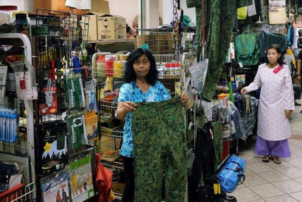 MASIH TERUS BERNIAGA: Cik Katy (depan) menunjukkan salah satu pakaian tentera yang dijual di kedainya, Zulaika Store, di Beach Road Army Market yang kini kian banyak dilawati mereka, khususnya golongan pelajar, yang datang untuk membeli peralatan perkhemahan dan ekspedisi. - Foto KHALID BABA