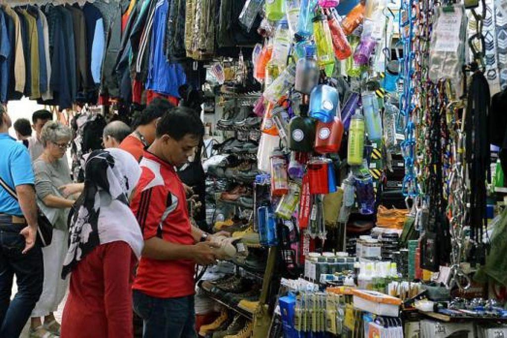 SIBUK MEMBELI: Encik Khyrul Ruthlie (kanan) bersama isterinya ketika mencari barang perkhemahan di Beach Road Army Market. - Foto KHALID BABA