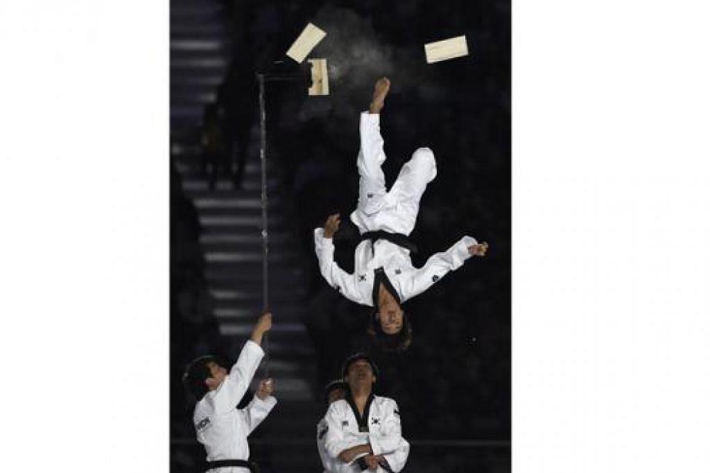 TERUNGGUL: Anggota Kukkiwon, iaitu Ibu Pejabat Taekwondo Dunia, menunjukkan kehebatan mereka di acara penutup. – Foto AFP
