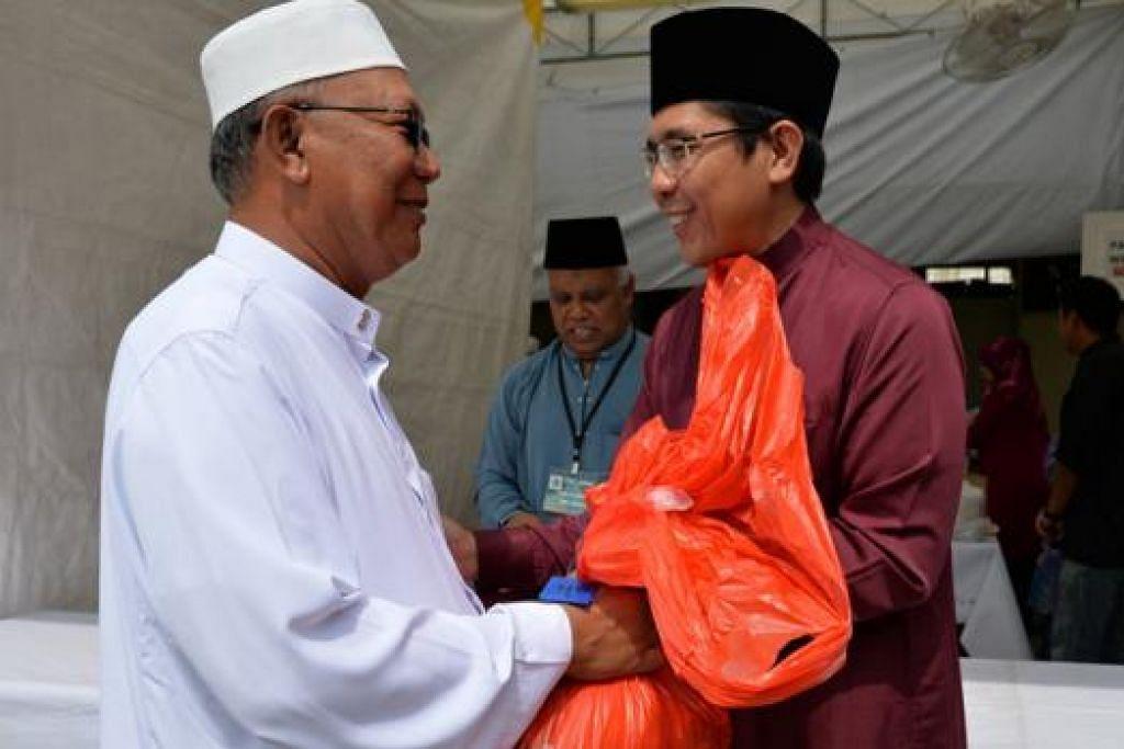 RAIKAN BERSAMA: Menteri Negara (Pembangunan Negara merangkap Pertahanan), Dr Mohd Maliki Osman, turut mengagihkan daging hasil ibadah korban yang dianjurkan Jamiyah Singapura di Rumah Peralihan Jamiyah, Darul Islah.
