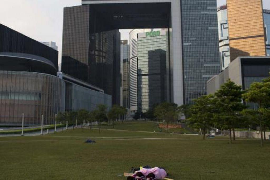 TERUS ADAKAN BANTAHAN: Penunjuk perasaan tidur di depan ibu pejabat pemerintah Hongkong awal semalam. Rakan-rakan mereka terus berdemo dan menyekat jalan raya utama ke kawasan pusat bandar. - Foto REUTERS