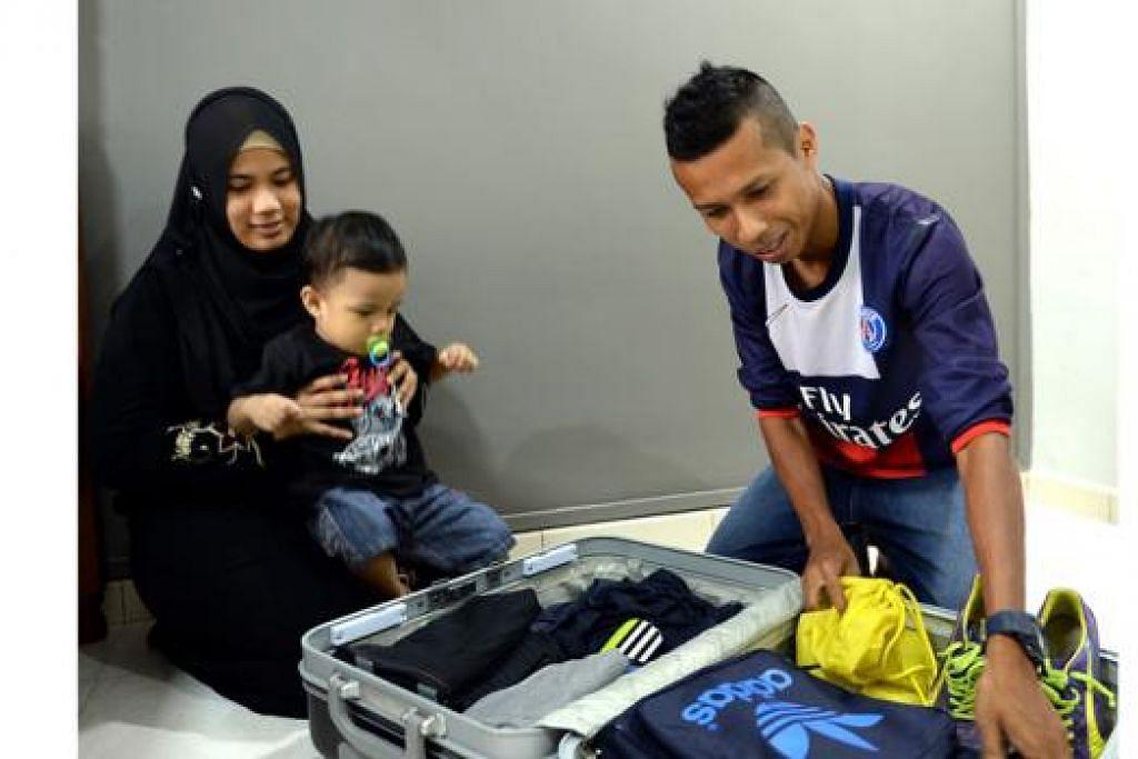 HARI ISTIMEWA: Ismadi Mukhtar bersiap-siap sebelum berangkat ke Hongkong bersama pasukan nasional Singapura. Bersamanya ialah isterinya, Cik Khairun-nisa Samsun, dan anaknya, Muhammad Azfer, 19 bulan. - Foto ZAINAL YAHYA