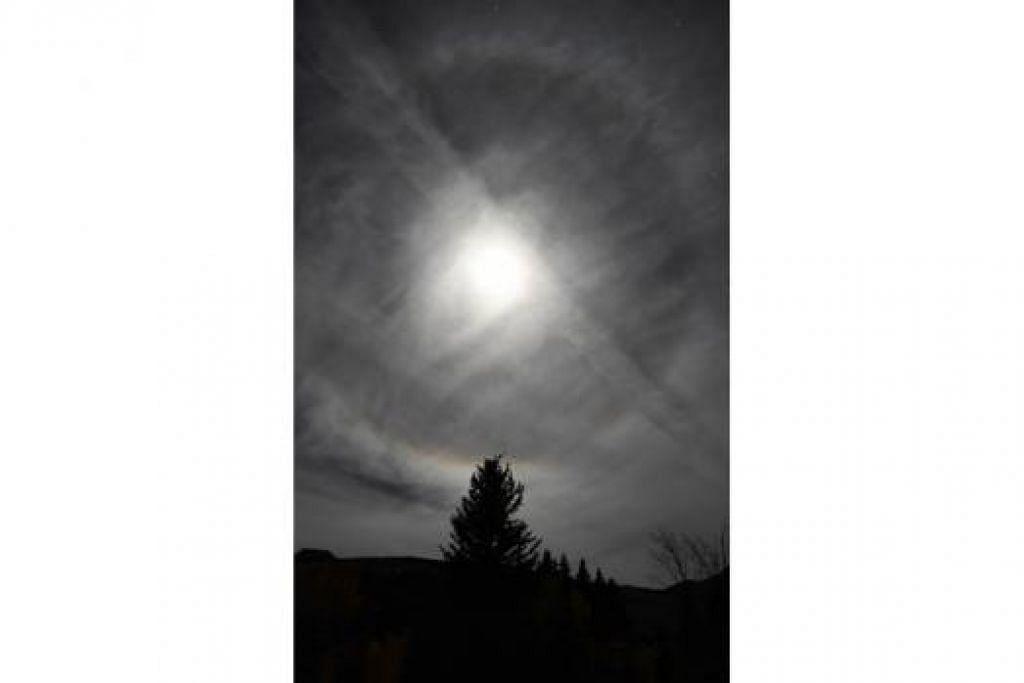 DI BALIK AWAN: Gambar ini menunjukkan gerhana bulan yang dilihat menerusi selaput tipis awan yang membentuk lingkaran cahaya atau 'moondog' di Crested Butte, Colorado, kelmarin. - Foto AFP