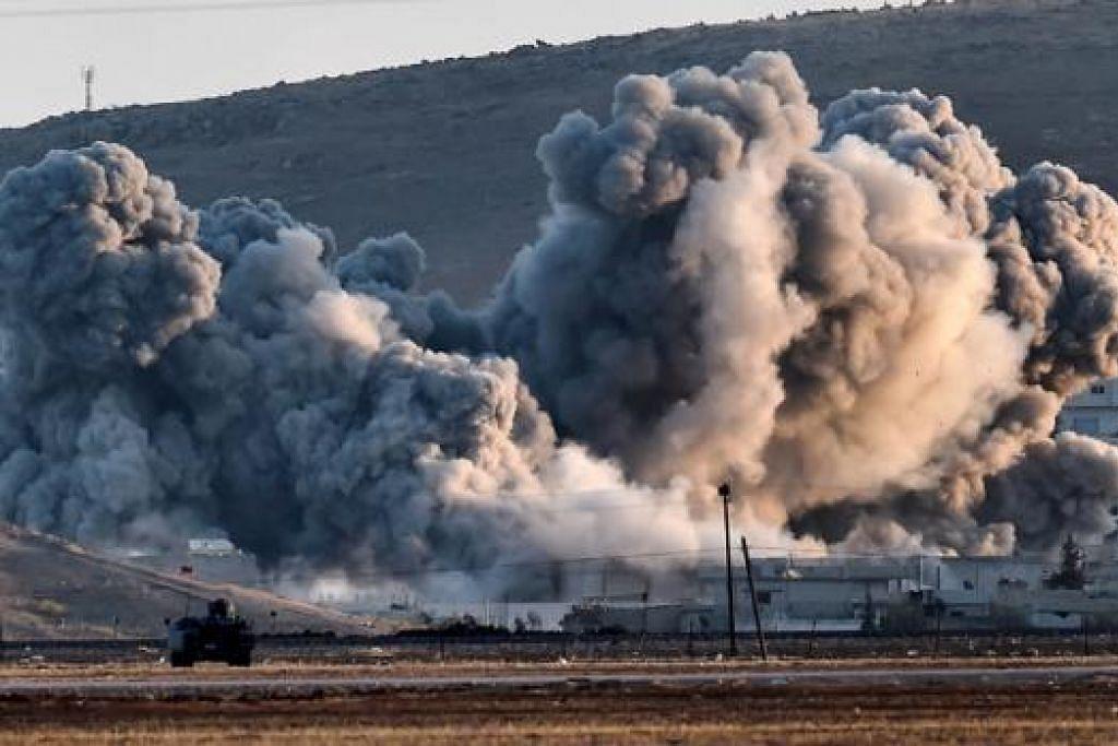 SERANG IS: Kepulan asap dilihat berdekatan bandar Kobane di Syria menyusuli serangan udara pasukan perikatan ke atas kedudukan militan IS yang cuba menawan bandar yang berdekatan sempadan Turkey. - Foto AFP