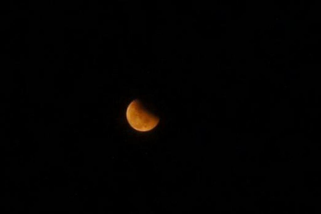 GERHANA BULAN PENUH: Jerebu menjadikan gerhana bulan kurang jelas kelihatan pada malam kelmarin. Gambar ini diambil sekitar 8 malam di langit Singapura. - Foto ABDUL MUHAIMIN ABDUL RAHMAN