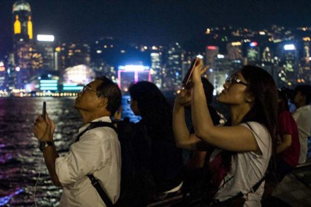 RAKAM FENOMENA: Orang ramai tidak melepaskan peluang memetik gambar gerhana bulan dari kawasan The Avenue of Stars di Hongkong kelmarin.