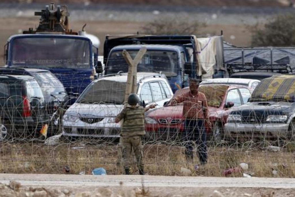 TENANG SEBELUM PERTEMPURAN?: Seorang penduduk Kurdi Syria menyerahkan rokok kepada seorang askar Turkey di kawasan sempadan Syria-Turkey semalam. - Foto REUTERS