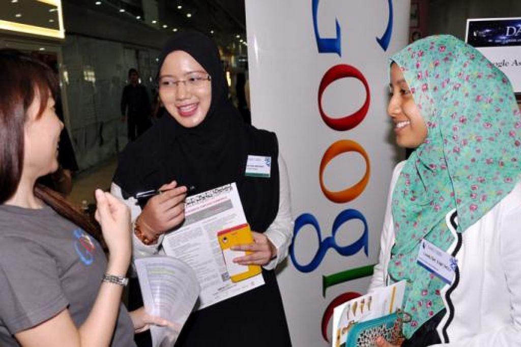 SEDIA CUBA BIDANG BARU: Cik Amalina (tengah) dan Cik Sharifah Fatimah (kanan) berbual dengan seorang kakitangan Google, Cik Cheryl Tang, di pameran kerjaya dan program bekerja sambil belajar SMU semalam. - Foto JOHARI RAHMAT