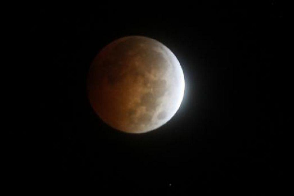 GERHANA BULAN PENUH: Bulan berubah warna semasa gerhana seperti dilihat dari Golden, Colorado Rabu lalu. - Foto REUTERS.