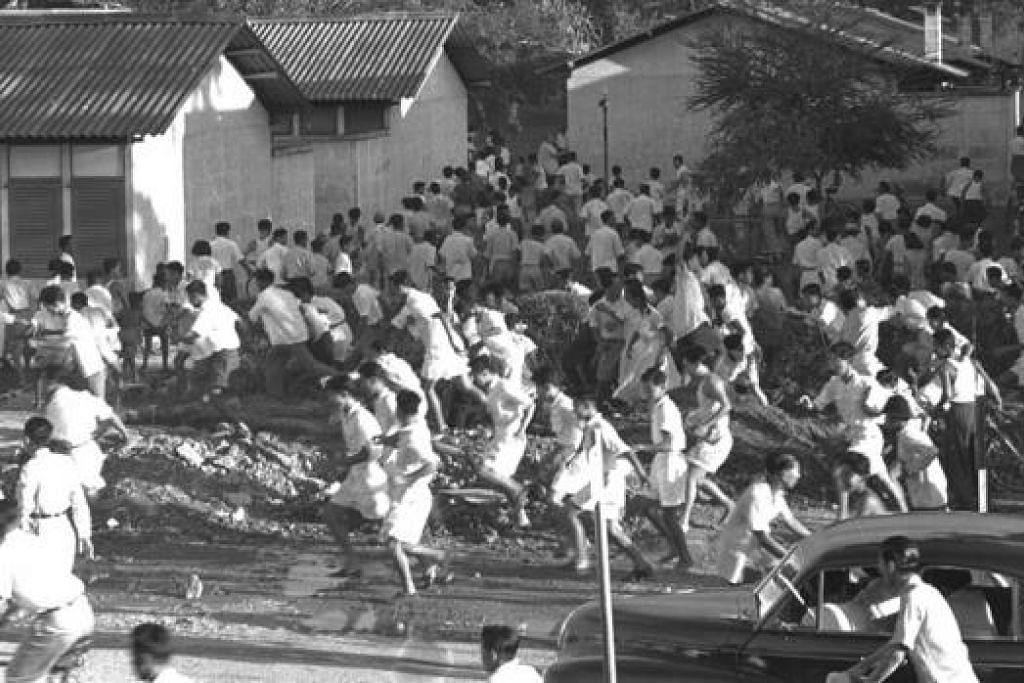 RUSUHAN DIDALANGI KOMUNIS; Penunjuk perasaan merusuh bersama pelajar dari sekolah Cina dan membakar bas syarikat Hock Lee walaupun disekat dengan gas pemedih mata oleh pihak keselamatan pada 11-12 Mei 1955. – Foto THE STRAITS TIMES