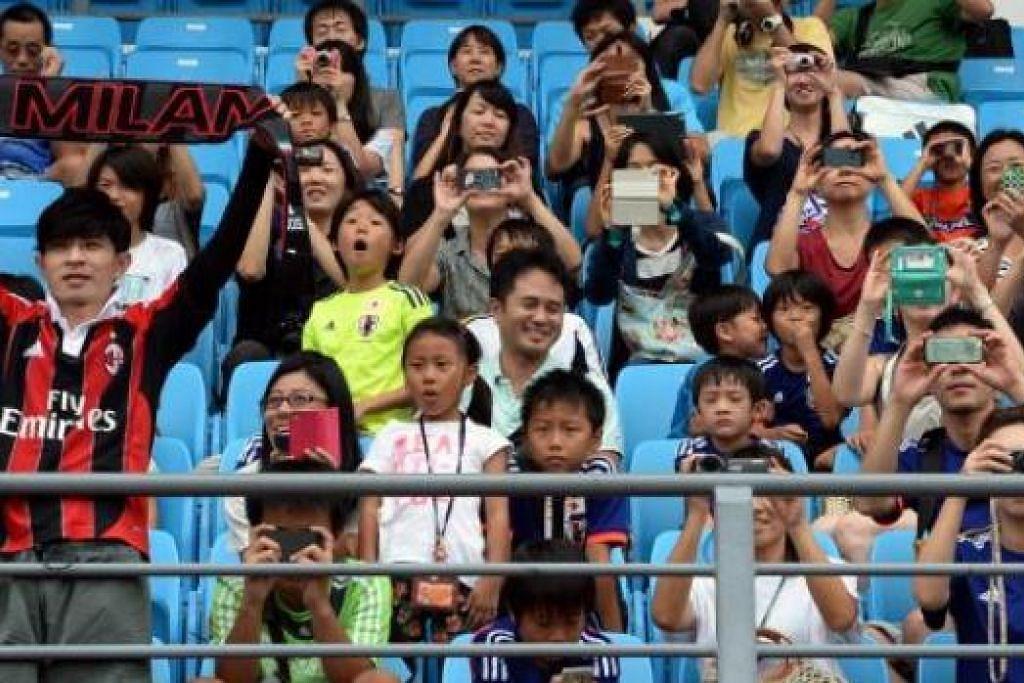 PEMINAT JEPUN ATAU AC MILAN?: Peminat ini – antara 700 penyokong pasukan itu yang berada di Stadium Bishan semalam – tentunya penyokong Keisuke Honda yang menyarungi jersi AC Milan. - Foto-foto ZAINAL YAHYA
