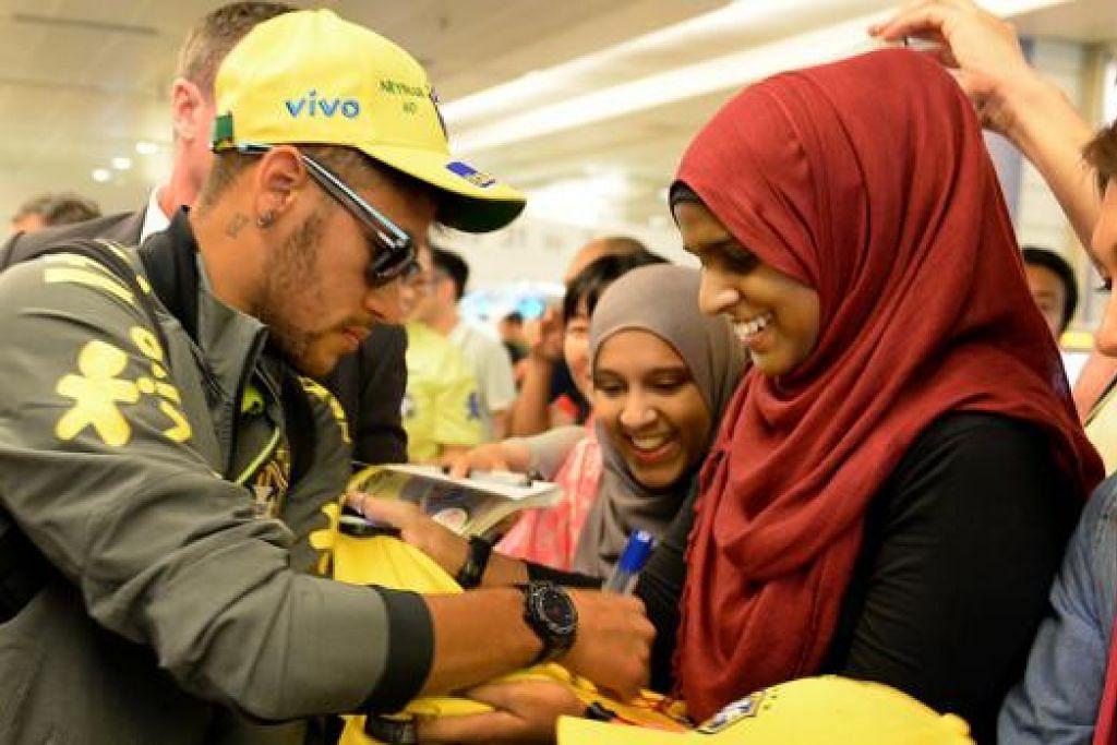 TEMUI IDOLA DARI DEKAT: Zahirah (bertudung merah) dan sepupunya, Sameerah, teruja melihat bintang Brazil, Neymar, melayani permintaan mereka. - Foto ZAINAL YAHYA
