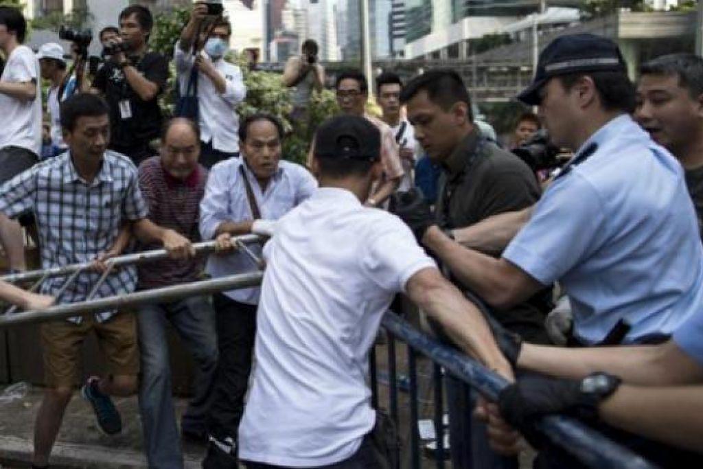 CUBA ALIHKAN PENGADANG: Kumpulan antikumpulan prodemokrasi yang bertopeng cuba mengalihkan pengadang yang dipasang oleh penunjuk perasaan prodemokrasi bagi menutup jalan di kawasan pusat kewangan di Hongkong, semalam. - Foto REUTERS