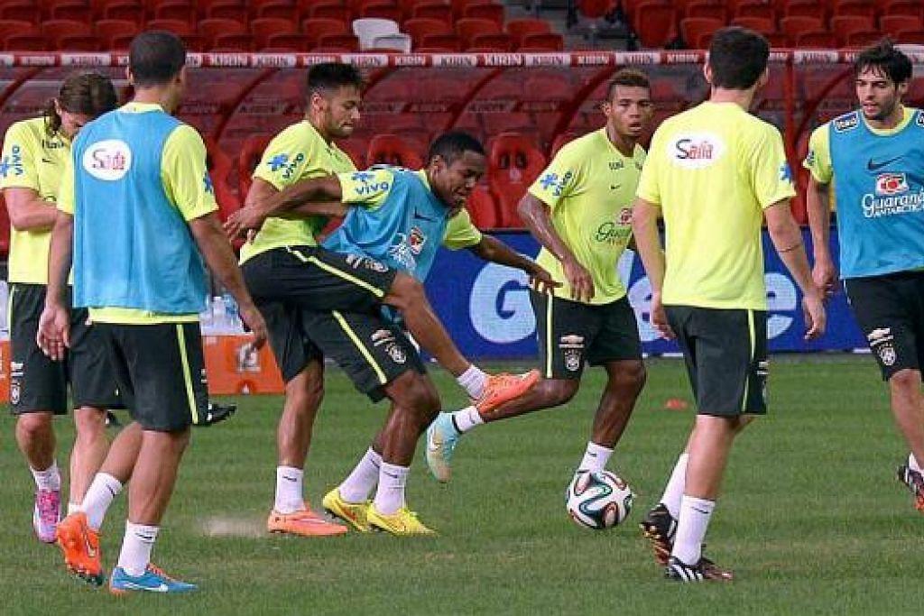 SERIUS BERLATIH: Bintang Brazil, Neymar (tiga dari kiri), cuba merebut bola daripada rakannya dalam satu sesi latihan yang diadakan di padang Stadium Negara petang semalam. Turut menyertai latihan itu ialah Kaka (kanan), yang diundang semula menyertai skuad Brazil. – Foto TAUFIK A. KADER
