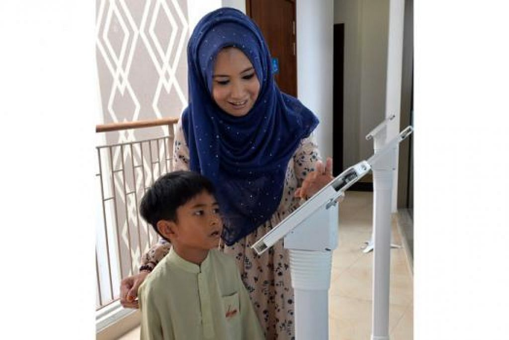 PROGRAM BARU: Cik Masturah sedang menunjukkan anaknya, Muhammad Aqil, doa-doa harian yang boleh diamalkan - antara bahan disediakan dalam edisi rumah Kids aLIVE.