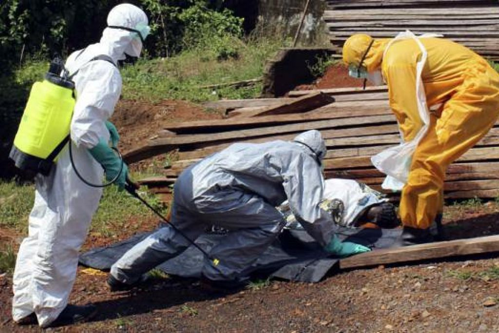 MEMINDAHKAN KORBAN WABAK: Pegawai Kesihatan memindahkan mayat wanita yang mati akibat Ebola di Freetown, Sierra Leone. - Foto REUTERS