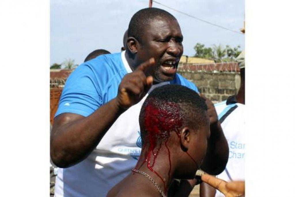 LAMBAT DIPINDAH: Kepala wanita ini berlumuran darah selepas dipukul pegawai polis apabila para penduduk meletakkan pengadang di jalan raya bagi mendesak mayat yang dijangkiti Ebola segera dipindahkan di Freetown, Sierra Leone. - Foto REUTERS