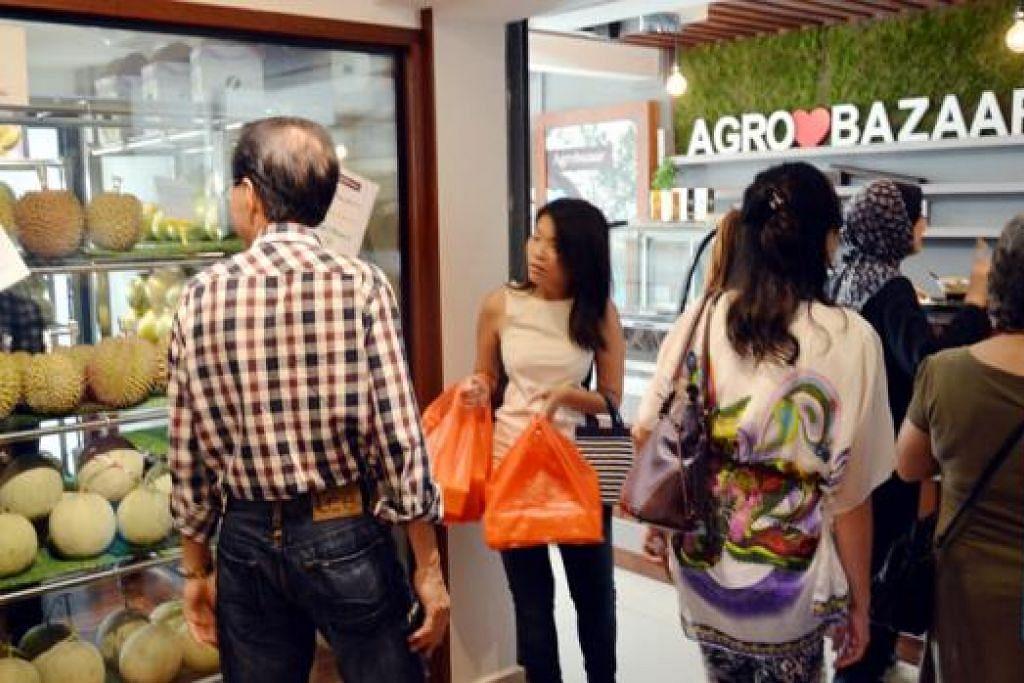 DI BAWAH SATU BUMBUNG: Pelanggan dilihat meninjau buah-buahan dan produk berasaskan pertanian dari Malaysia yang dijual di Agrobazaar yang mula beroperasi di Sultan Gate pada Ogos lalu. - Foto-foto JOHARI RAHMAT
