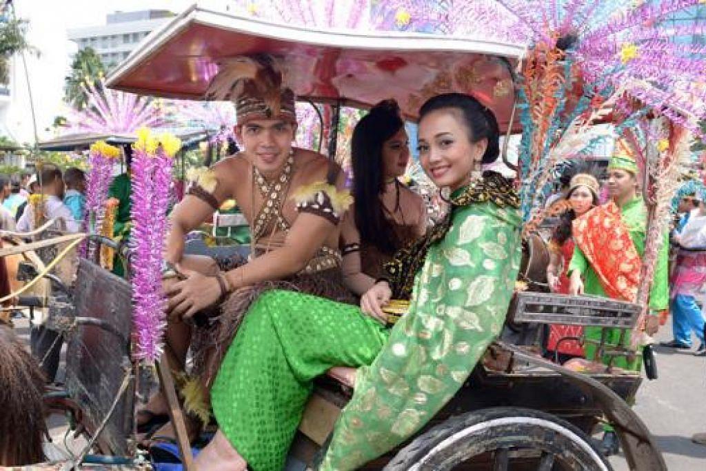 SIAP MENUNGGU: Peserta dengan pakaian tradisional siap menanti ketibaan Encik Jokowi dan Encik Kalla untuk menyertai mereka dalam perarakan menuju ke Istana Negara semalam. - Foto THE STRAITS TIMES