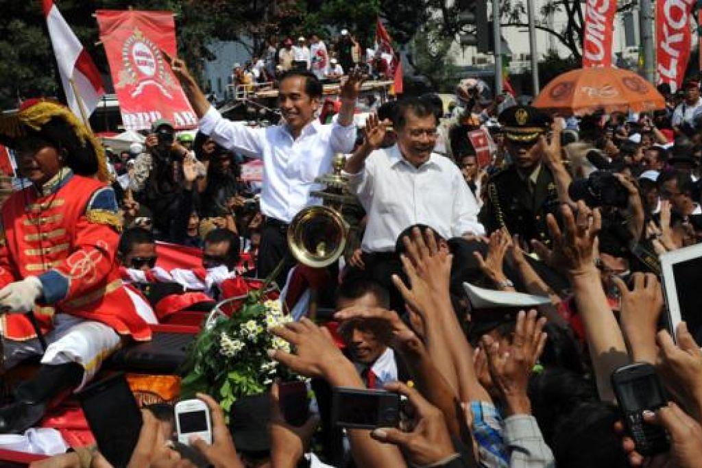 KETIBAAN DIALU-ALUKAN: Encik Jokowi (berbaju putih tanpa cermin mata - tengah) dan Encik Kalla (di sebelahnya) disambut dengan begitu meriah oleh rakyat semasa pedati yang mereka naiki melalui jalan menuju ke Istana Negara semalam. - Foto AFP.