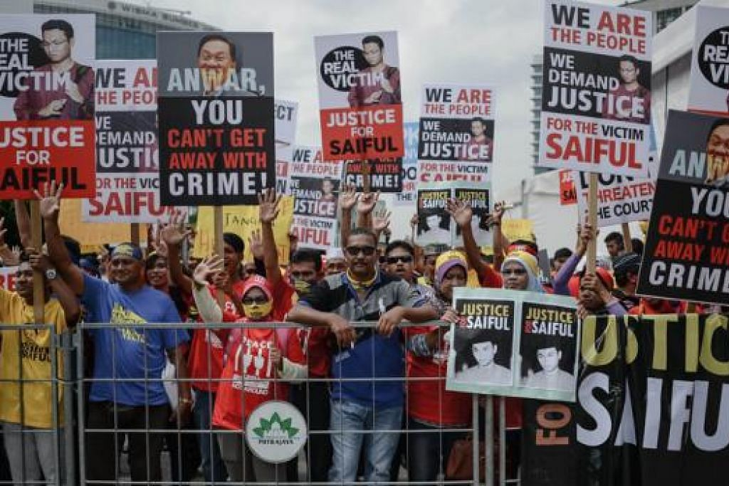 ANTARA DUA PENYOKONG: Penyokong Datuk Seri Anwar Ibrahim lantang di luar mahkamah. Bagaimanapun penyokong Encik Mohamad Saiful Bukhari Azlan tidak kurang lantang memaparkan sepanduk dan melaung-laungkan slogan anti Datuk Anwar, semalam. - Foto-foto AFP