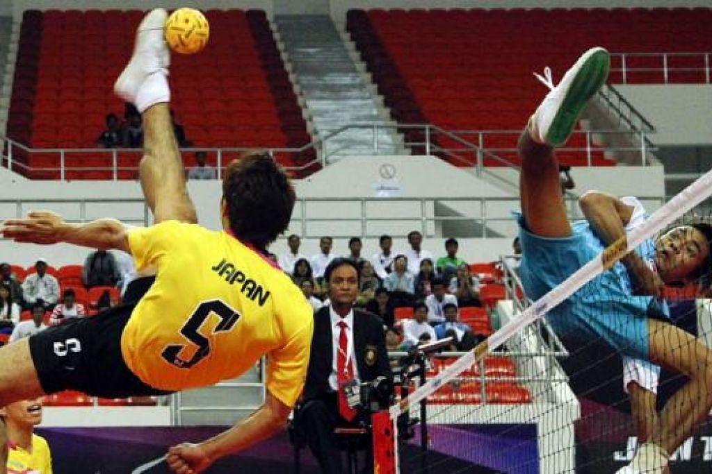 PAMER AKSI HEBAT: Penyerang nasional, Muhammad A'fif Sapiee (jersi biru), melompat tinggi untuk cuba mengadang sepakan libas penyerang Jepun. Singapura berjaya mengatasi lawan mereka itu 2-0 di Stadium Tertutup Wunna Theikdi di Myanmar pagi semalam. - Foto ISTAF
