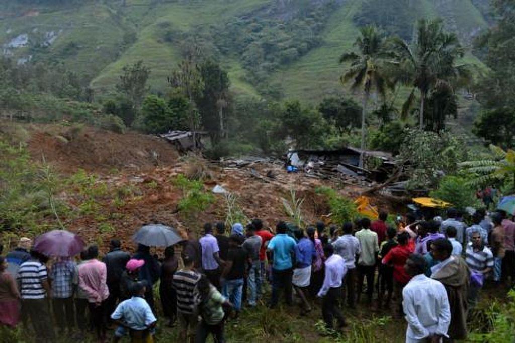 KESAN TANAH RUNTUH: Para penduduk melihat sebuah bangunan yang musnah di kawasan kejadian tanah runtuh akibat hujan monsun di kampung Koslanda di tengah Sri Lanka kelmarin. - Foto AFP
