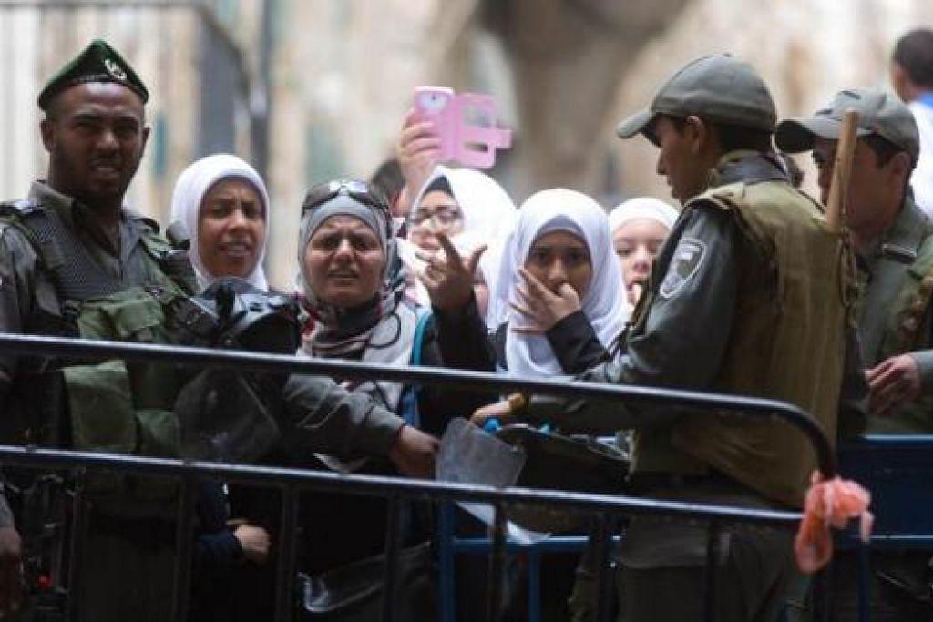 HALANG MASUK: Polis Israel menghalang wanita Palestin memasuki perkarangan Masjid Al-Aqsa selepas pihak berkuasa Israel menutup perkarangan masjid itu buat sementara. - Foto AFP