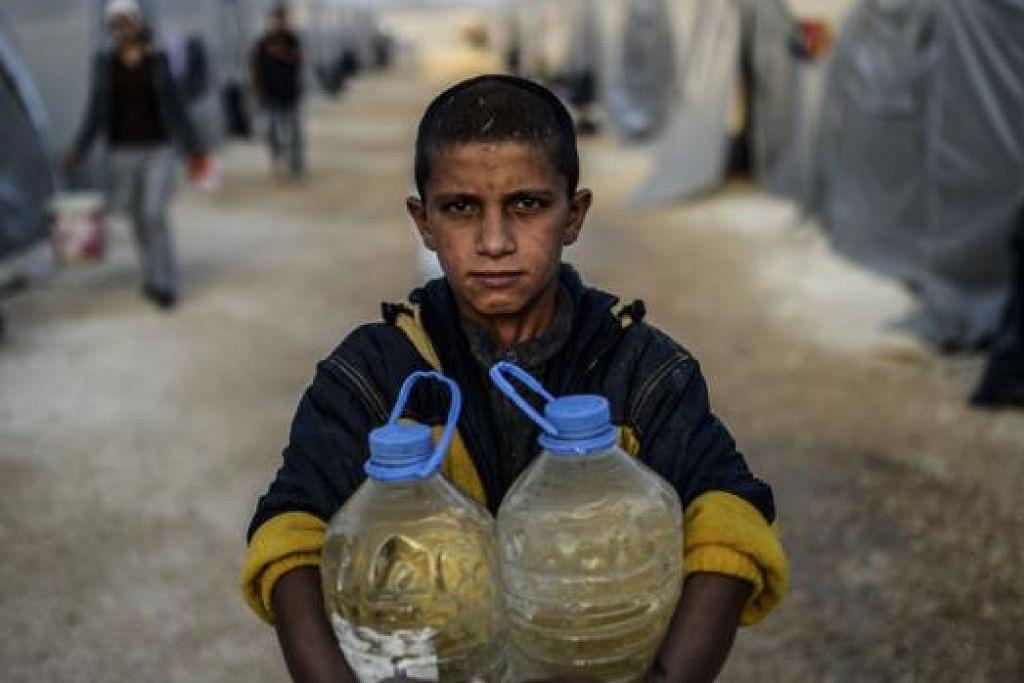 KRISIS KELIHATAN MASIH BELUM ADA PENGHUJUNG: Seorang kanak-kanak Syria membawa bekalan air kepada anggota keluarganya di khemah pelarian di Suruc, wilayah Sanliurfa. Krisis di Syria telah mengorbankan lebih 180,000 orang dan menyebabkan hampir separuh penduduk negara itu meninggalkan kediaman masing-masing. - Foto AFP