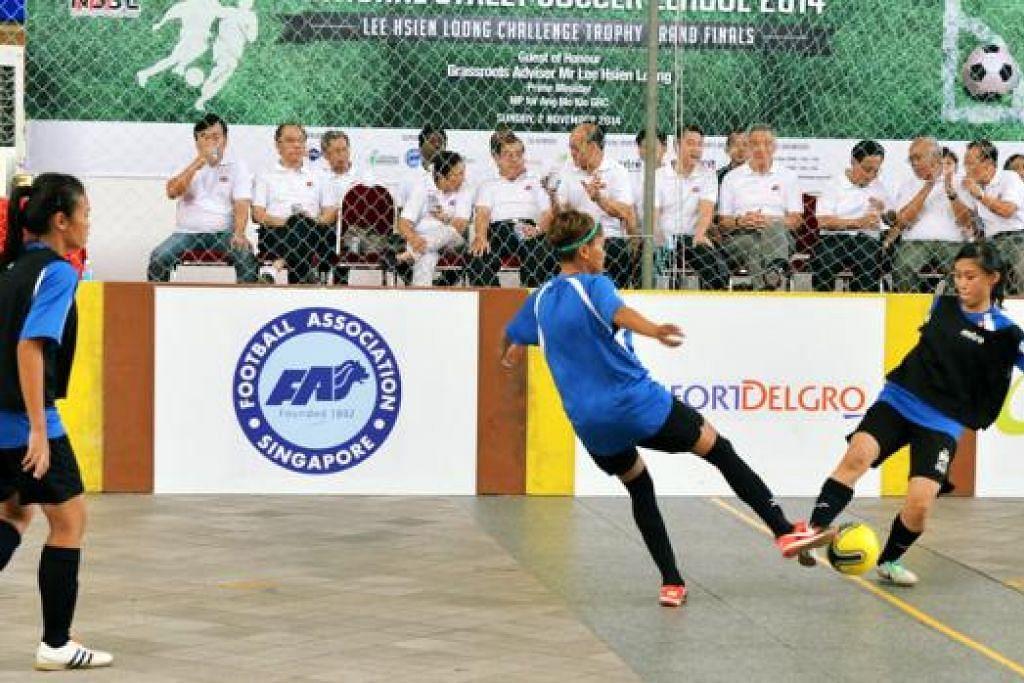 SIAPA CEPAT, DIA PUNYA: Dua pemain daripada pasukan EB Sports B dan Chapalang berebut bola dalam final kategori Terbuka Wanita yang dimenangi EB Sports B. Turut menyaksikan pertarungan itu ialah tetamu terhormat, Perdana Menteri Lee Hsien Loong (duduk, lima dari kanan).