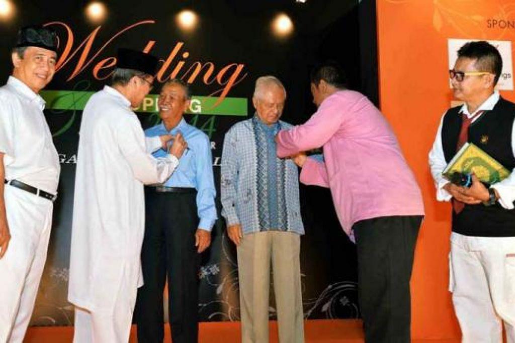 WAKAF INSAN: Setiausaha PSNU, Haji Hadari As'at (dua dari kiri), dan bendahari PSNU, Encik Sharuddin Sogol (baju merah jambu), menyematkan lencana Sekolah Menengah Sang Nila Utama di baju Encik Yatiman Yusof (tiga dari kiri) dan Haji Wan Hussin Zoohri (empat dari kiri) semasa majlis pelancaran Wakaf Insan. Bersama mereka ialah presiden PSNU, Haji Mohd Khamin Said (kiri), dan setiausaha eksekutif PSNU, Ustaz Idris Ahmad (kanan). - Foto KHALID BABA
