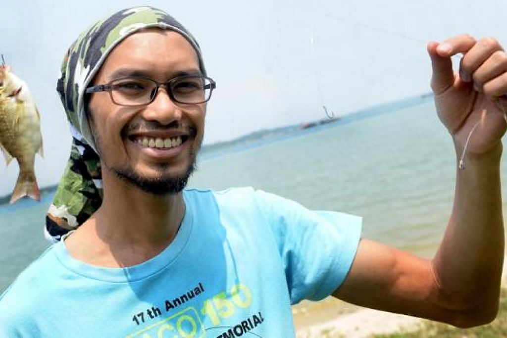 PANCING DI PANTAI: Encik Mohamed Matiin hanya menggunakan umpan cacing bagi menangkap ikan mempinang di pantai Pasir Ris Park. - Foto TAUFIK A. KADER