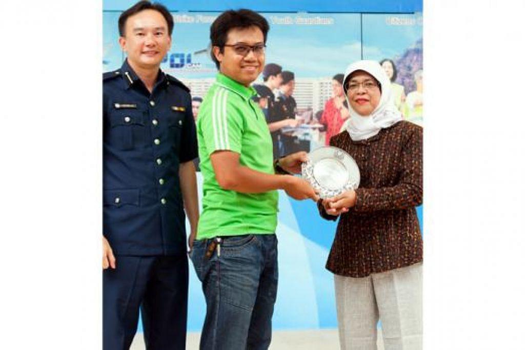 BERSEMANGAT RAKYAT: Encik Khairul menerima Anugerah Semangat Rakyat daripada Encik Wilson Lim dan Cik Halimah Yacob. - Foto: SINGAPORE POLICE FORCE