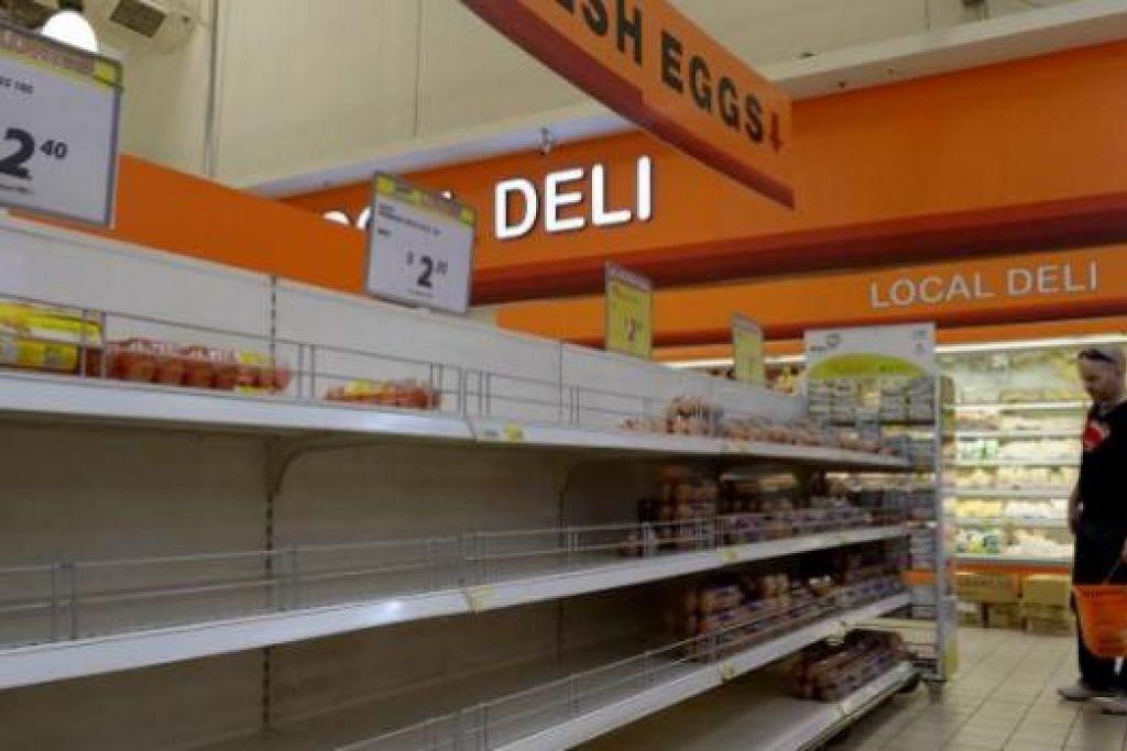 BEKALAN TELUR KURANG: Seorang pelanggan yang hendak membeli telur di pasar raya Giant semalam tiada banyak pilihan. - Foto TUKIMAN WARJI