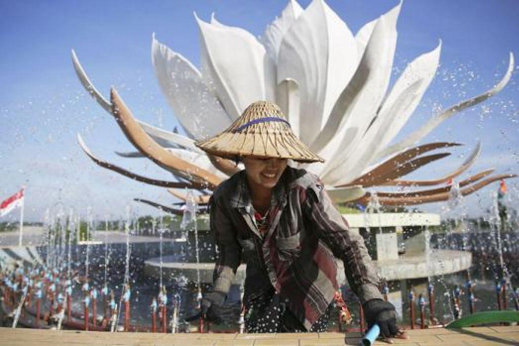 BUAT PERSIAPAN BAGI MENYAMBUT KEHADIRAN PEMIMPIN DARI LUAR NEGARA: Seorang gadis keluar daripada kolam selepas membuka paip air pancutan yang menghiasi bandar Naypyitaw, Myanmar. Negara itu akan menganjurkan Sidang Puncak Asean selama dua hari bermula esok. - Foto REUTERS